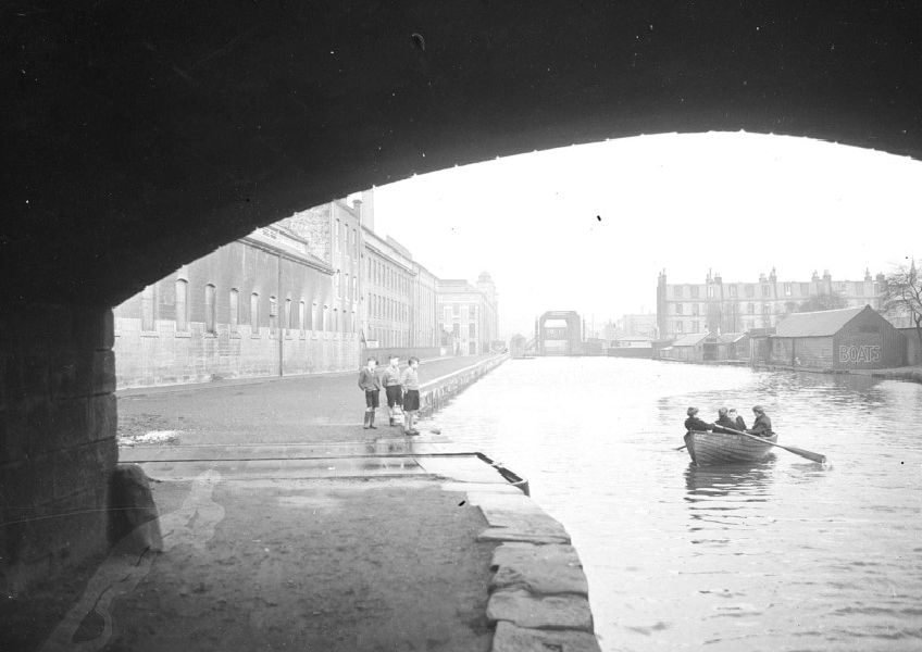 Young rowers on the Union Canal between Gilmore Place and Fountainbridge in Edinburgh looking towards the Canal terminus.  'North British Rubber Mills on left now demolished.