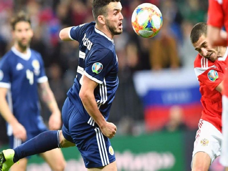 John McGinn battles for possession during the 4-0 loss in Russia.