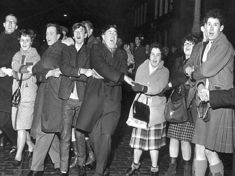 People singing Auld Lang's Syne during New Year at the Tron, Edinburgh 1964.