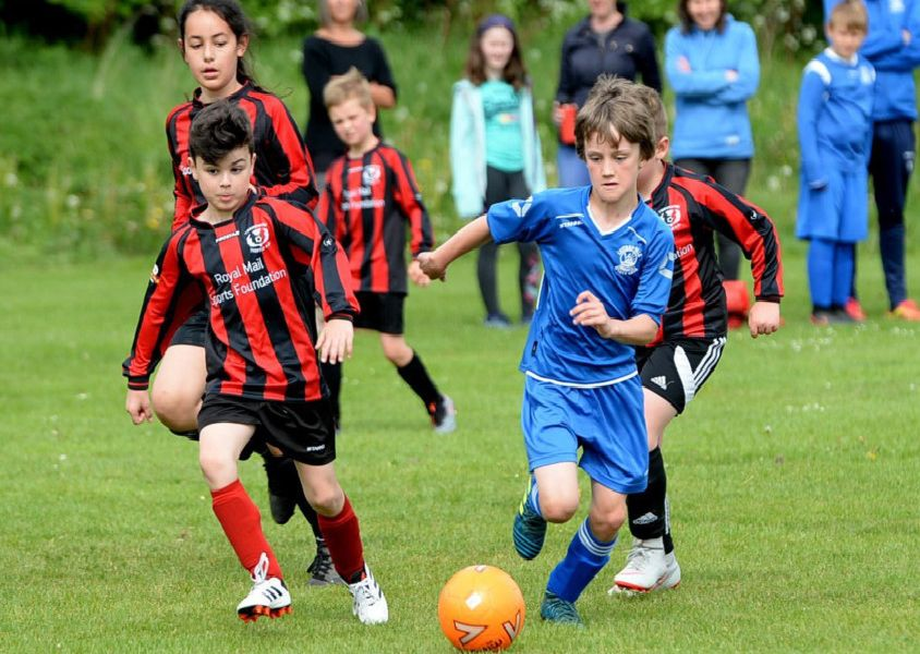 Leithen Vale (in blue) get the ball away from Tweeddale Thistle.