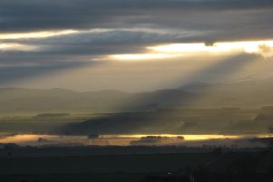 Shafts of morning sunlight pierce their way through cloud over the Cheviots.