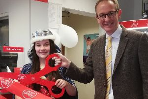 John Lamont MP, assisted  by this year's Eyemouth Herring Queen Isla Purvis, cut the ribbon to officially open Eyemouth Post Office.