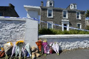 Tributes were left outside the house where 6-year-old Alesha MacPhail had been staying outside Rothesay.