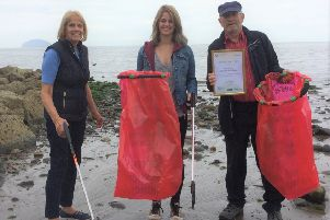 Alistair Wallace, who has won a Keep Scotland Beautiful award, cleaning up Girvan beach with Ruth Wallace and Kirsty McWilliams.