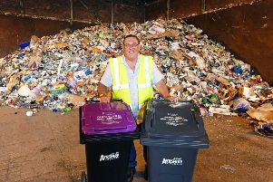 Councillor Ian Cochrane, portfolio holder for sustainability and environment shows the two new bins being introduced in front of one day's worth of recycling collections (roughly 50 tonnes).