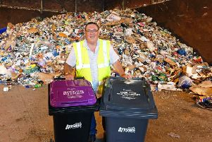 Councillor Ian Cochrane, portfolio holder for sustainability and environment shows the two new bins that have been introduced, in front of one day's worth of recycling collections (roughly 50 tonnes).