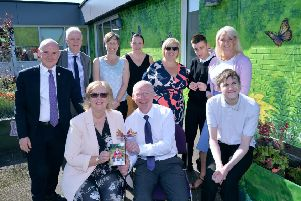 Anne and Andrew Alexander hold a picture of their daughter Kirsty as the new butterfly-themed mural is unveiled in her memory at Redburn School