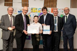 Grace Littlejohn  receives her award at the Scottish Parliament. She is pictured with left to right, Stewart Steveson MSP, Deputy First Minister John Swinney, Alexander Burnett MSP, Thane Lawrie, Scarf, and Brian Lironi, Scottish Water