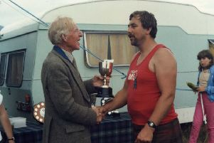"""Mike Gill being presented with his trophy as a """"heavy"""" event winner in the 80s"""