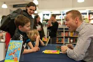 Sir Chris Hoy signs copies of his book for six-year-old Hamish Mayes. Picture: Andrew O'Brien