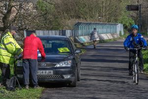 A passing cyclist looks askance at the surveyors with their parked car. Picture: Scott Taylor