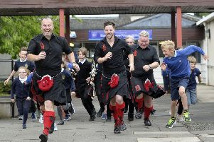 The Red Hot Chilli Pipers and pupils from King's Meadow Primary School rehearse for the music video. Picture: Neil Hanna