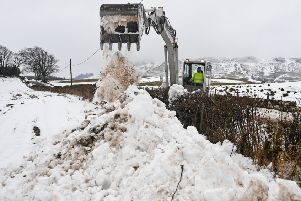 A man clears the B818 with a digger in Fintry as police advised motorists to drive with caution while weather warnings persist. Picture: Getty