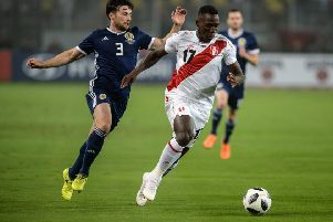 Lewis Stevenson, one of seven debutants, vies for the ball with Peru's Luis Advincula. Picture: Ernesto Benavides/AFP/Getty Images