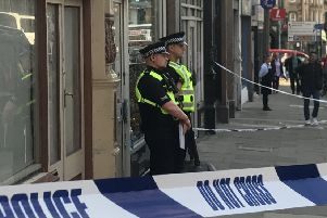 Officers stand guard outside a shop on Home Street