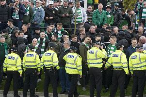 Celtic fans face a line of police officers separating them from Rangers supporters. Picture: John Devlin