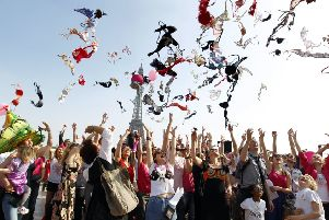 Campaigners in Paris hurl their bras into the air as part of a campaign to raise awareness of breast cancer. Picture: AFP/Getty