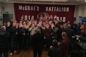 A group pose with Tommy Robinson masks in front of a McCrae's Battalion Hearts flag. Picture: Instagram/realtommyrobinson