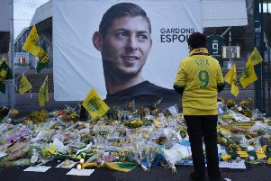 A Nantes fan stops by a poster of Emiliano Sala. Picture: AP