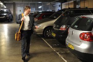 A man walks in an office car park.