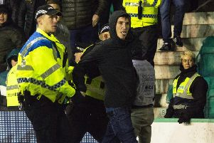 Cameron Mack is led away from Police after running onto the park and confronting James Tavernier