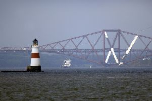 View of the Forth Bridge and lighthouse in the Firth of Forth.