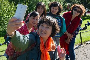 Tourists stop for a picture in Princes Street Gardens. Picture: Scott Taylor