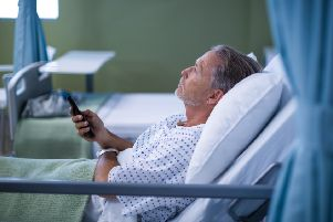Patient watching television on bed at the hospital.