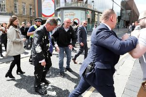 Brexit Party leader Nigel gestures after being hit with a milkshake while arriving for a Brexit Party campaign event in Newcastle