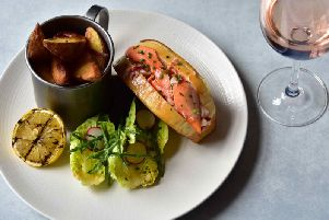 The Scottish lobster is served in a roll, drizzled with lemon and herb butter, and served with hand-cut chips and a side salad.