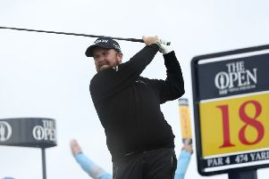 Shane Lowry watches his tee shot at the 18th, having put together a round to lie one shot off the lead