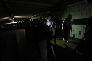 Commuters walk in darkness at London's Clapham Junction station. Picture: PA