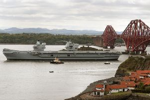 The aircraft carrier HMS Queen Elizabeth passes the Forth Rail Bridge as it leaves the Firth of Forth following maintenance at the Rosyth Dockyards, where some of the 2,500 shipbuilding jobs secured by the government will go. Picture: PA