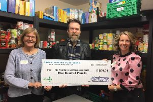Sam Lucas hands over the cheque to Aberdeenshire North Foodbank staff.