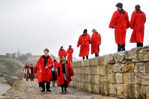 Students from the University of St Andrews walk along the harbour wall wearing their infamous red gowns.