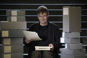 Ian Rankin holding his 1984 manuscript for his first published novel Flood, with some of the 50 boxes of his own personal archive which he is donating to the National Library of Scotland. Pic: SWNS
