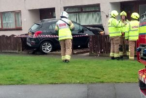Emergency services are on the scene in Kirkcaldy after a car collided with a property in Lindores Drive. Pic: Scott McCartney.
