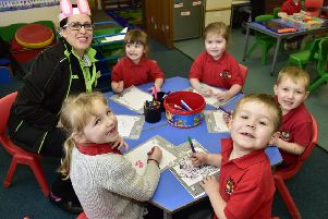 CAROLYN TAYLOR FROM ASDA,FRASERBURGH COLOURING IN PICTURES WITH  THE NURSERY CLASS AT LOCHPOTS PRIMARY SCHOOL.