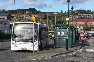 A bus picking up passengers in Hawick's Mart Street.