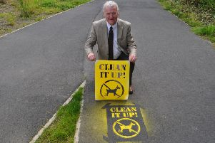 SBC councillor David Paterson with the new stencil  promoting Scottish Borders Council's dog fouling message on pavements and paths across the region.