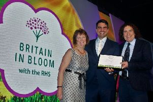 Marj Lochtie and Ron Smith receive the Britain in Bloom gold certificate from TV presenter Chris Bavin, centre.
