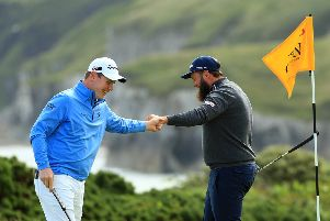 Andrew Johnston of England high fives Robert MacIntyre of Scotland on the 5th green during the first round of the 148th Open Championship  (Photo by Mike Ehrmann/Getty Images)
