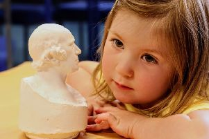 Little Bethany Stevens of Bo'ness checks out the bust of inventor James Watt on show at Bo'ness Library.
