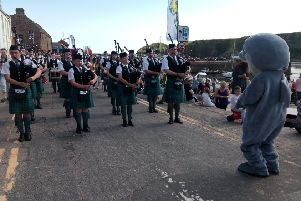 Stonehaven's Open Air Pool mascot, Splasher the Dolphin, opened the Festival and judged the Sandcastle Competition. Here he is being entertained by Newtonhill Pipe Band.