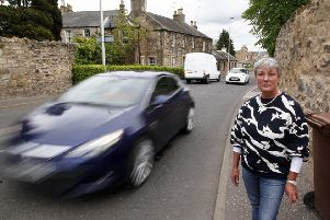 Resident Fiona Gilbert  next to a busy road in Bonnyrigg