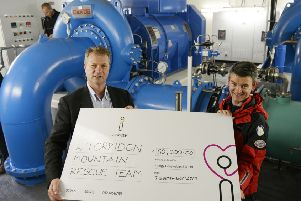 Torridon Mountain Rescue Team member Richard Cockburn accepts cheque from Hans Bunting, Chief Operating Officer, Renewables innogy SE, in the Grudie Hydro Electric scheme power station. Picture: Iain Ferguson/contributed