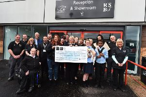 Audrey McJimpsey, training manager at RSBi, and RSBi staff hold up a cheque for �2,300 raised by the sports fun day. Picture: Contributed