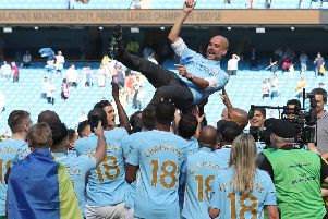 Manchester City players hoist manager Pep Guardiola as they celebrate their title triumph. Picture: PA