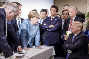 Angela Merkel looks like she is giving Donald Trump a row while the US President exudes a toddler-like defiance. Picture: AP