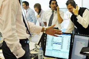 Currency traders at Worldwide Currencies Ltd in London's Canary Wharf stand at their desks to cold call during 'power hour'. So-called 'robo-trading' is reducing demand for such practices. Picture: PA